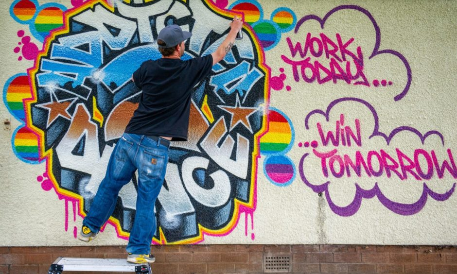 Adam Milroy working on a graffiti commission in Dundee