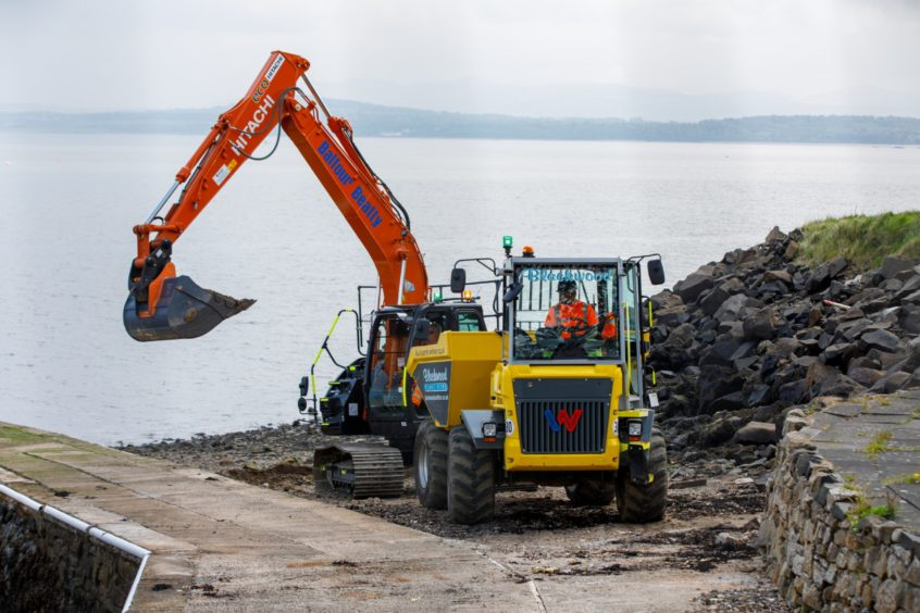 A digger clears contaminated material from the beach at Dalgety Bay.