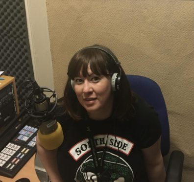 Lisa May Young sitting in front of her microphone