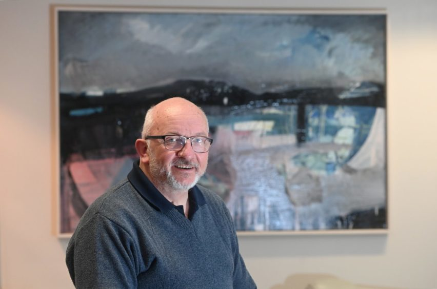 A smiling Howard Drysdale standing in front of a harbour-inspired painting