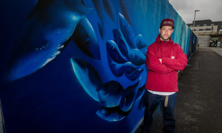 Adam standing in front of his mural