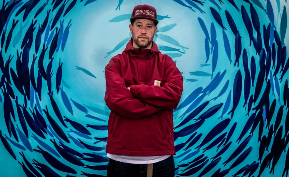 Dundee graffiti artist Adam Milroy in front of his mural