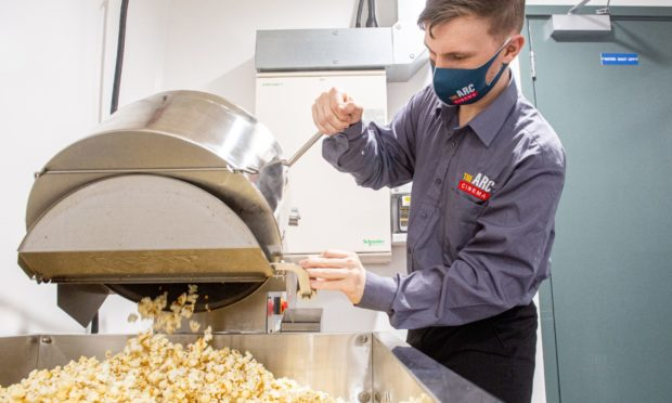 As the Arc cinema in Peterhead prepares for opening again on Monday, staff member Chris McLatchie gives the popcorn machine a run through.