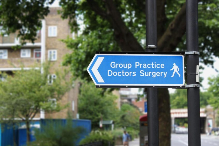 A blue sign pointing the way to a GP surgery