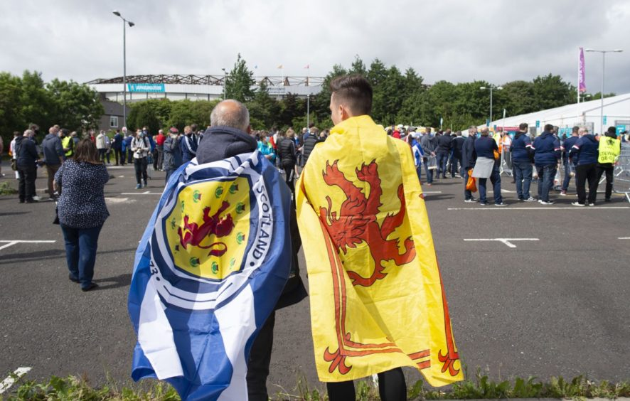 Draped in flags, two Scotland fans make their way to Hampden.