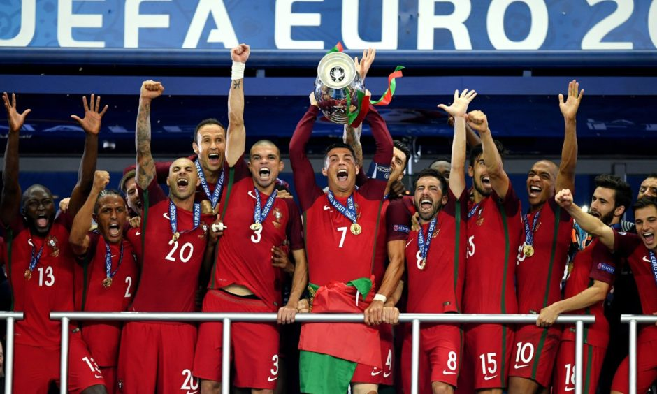 Cristiano Ronaldo of Portugal, centre, lifts the Henri Delaunay trophy after his side defeated France 1-0 in the final of Euro 2016.