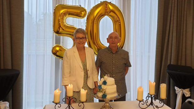Joe and Doris Boag stand in front of two gold ballons (one 5 and one 0), behind a cake, celebrating their 50th wedding anniversary.