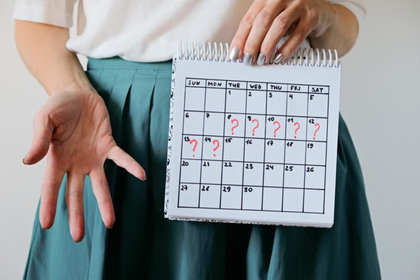 A woman holding a calendar with question marks written in each day.
