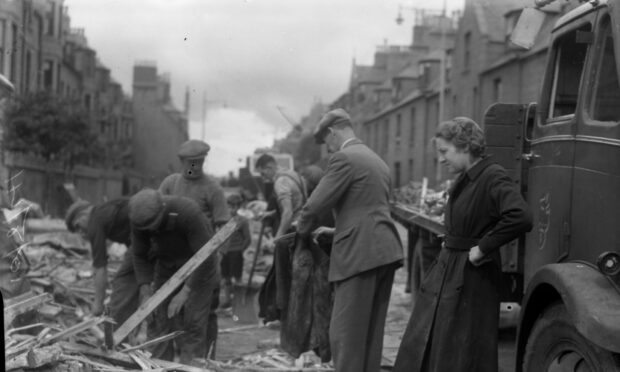A black and white image of men clearing rubble following the Peterhead bombing. A woman looks on, hands on hips, in a dark coat as the suited men, all wearing flat caps search through piles of wood and rubble.