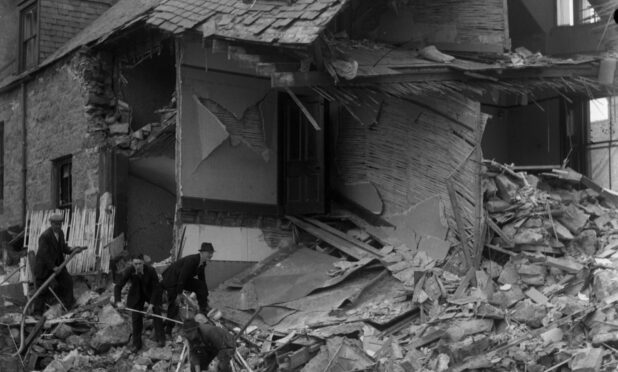 A black and white picture showing the gable end of a house completely destroyed by the Peterhead bombing. Three men in suits and hats shovel debris.