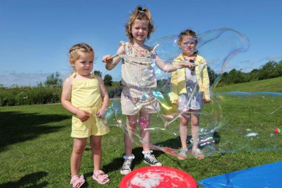 Mia Adams (3), Halle Costello (5) and Zara Adams (5) play with bubbles