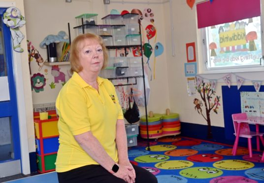Kiddiwinks manager Carolyn Harper sitting on the floor of the playgroup