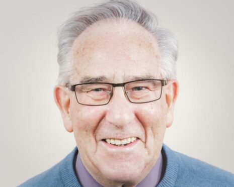 A close up shot of Rev Ken Gordon pictured in his later years. His hair is greying and he's wearing black thin-rimmed glasses with a wide smile.