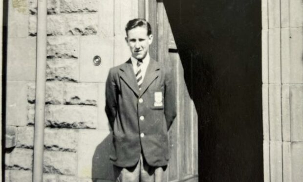 A young Ken Gordon is shown at the stone doorway of George Heriot school. He is wearing a striped school tie and badged blazer.