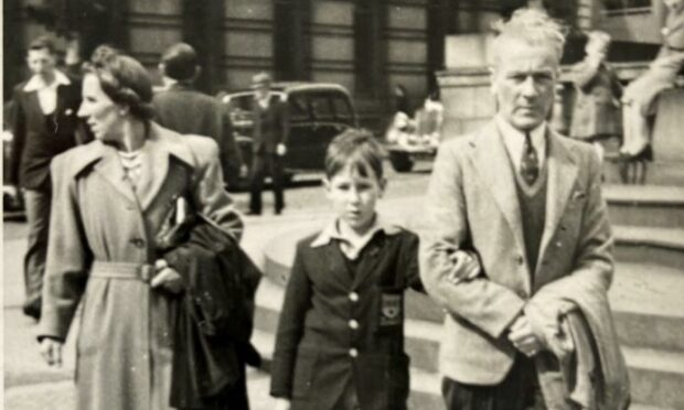 A black and white picture showing a young Ken Gordon holding the arm of his father, while his mother walks behind them on a busy Aberdeen street. Black cars and crowds are also shown.