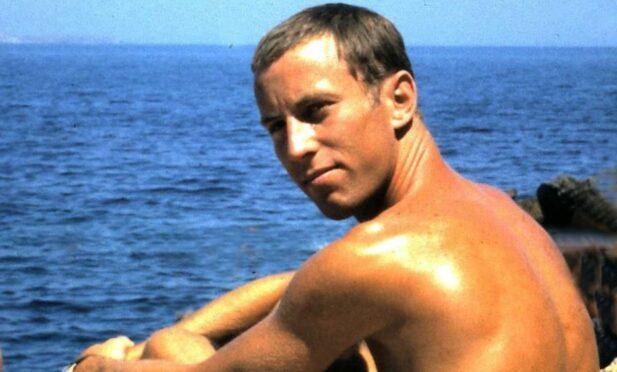Pictured as a young adult, posing shirtless by the sea in Greece is Iain McIntosh.