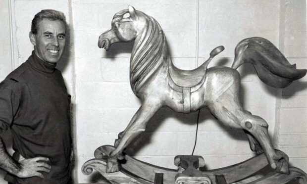 Black and white image of Iain McIntosh standing to the left of a wooden rocking horse he made for Harrods department store