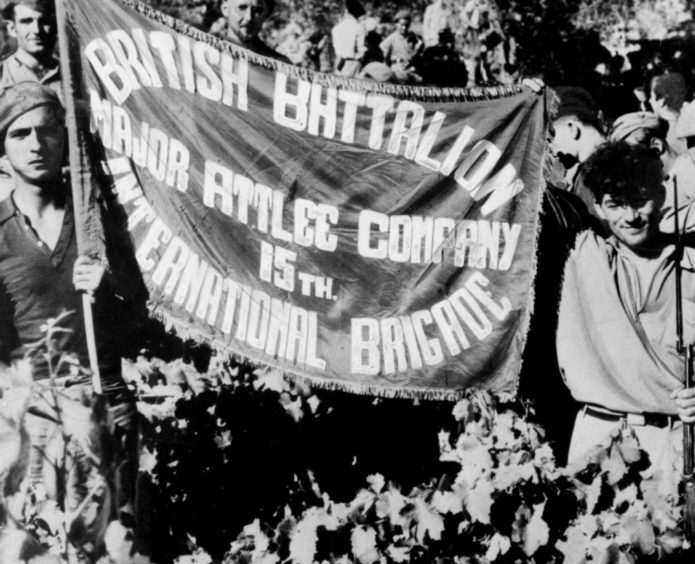 Members of the British Battalion, Major Attlee Company, 15th International Brigade, displaying their banner during a lull in the fighting.