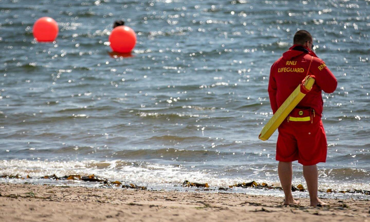 An RNLI lifeguard patrolling on a beach