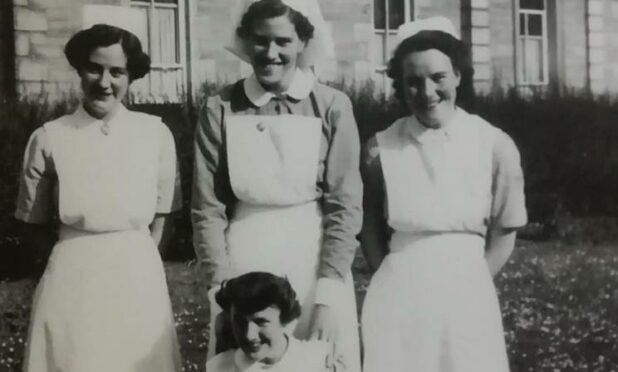 black and white image of trainee nurses pictured outside hospital building, wearing white nurses' hats and aprons. Evelyn MacKenzie is shown sitting front and centre of the image