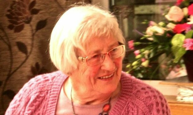 Smiling in an unposed way, Evie MacKenzie is pictured wearing a pink knitted cardigan, pink t-shirt and multi-coloured necklace. She has flowers behind her and she has glasses on.