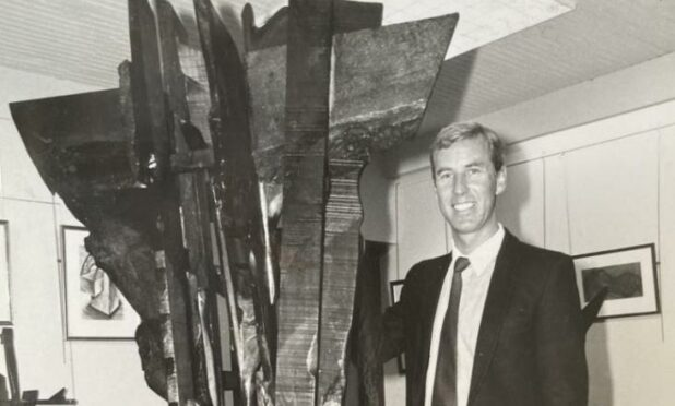 Black and white image of Iain McIntosh beside a huge, jagged wooden sculpture that towers over him.