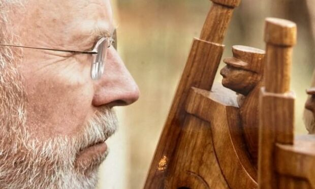 A spectacle-wearing Iain McIntosh looks closely at a wooden sculpture he has made