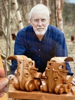 Coloured picture of a white-haired Iain McIntosh pictured in a blue shirt behind a highly intricate wooden sculpture