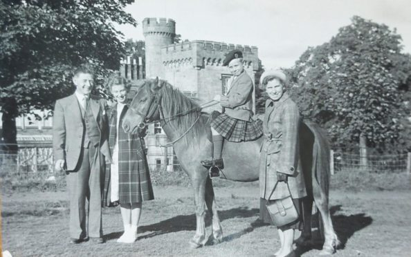A black and white photo of James and Barbara McIntosh, beside Iain - wearing a kilt and beret atop a horse, with daughter Sheila who is wearing a tartan swing coat. The photo is staged in front of a castle.