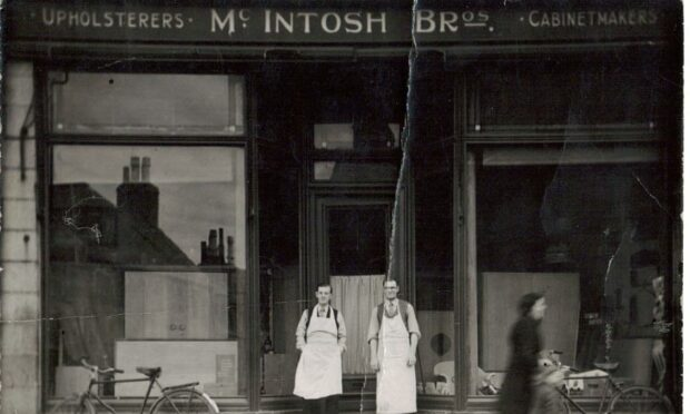 James and Bill McIntosh are pictured in a black and white shot, outside the shop they owned in Peterhead. They are in front of a high-ceilinged and large windowed shop exterior wearing white aprons over shirts and ties.