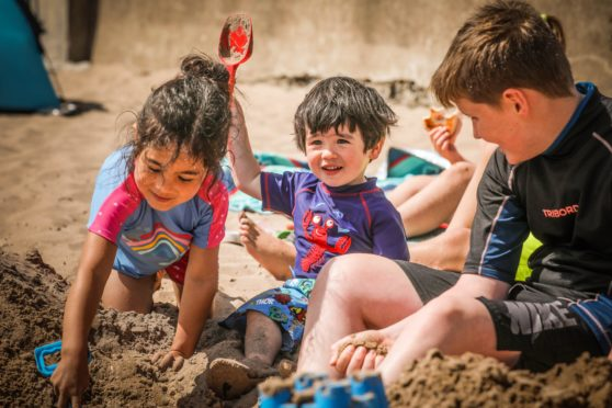 Picture shows; Rosie Cheng, 6, and Theo Cheng, 2, play in the sand alongside Finlay Mack, 11.