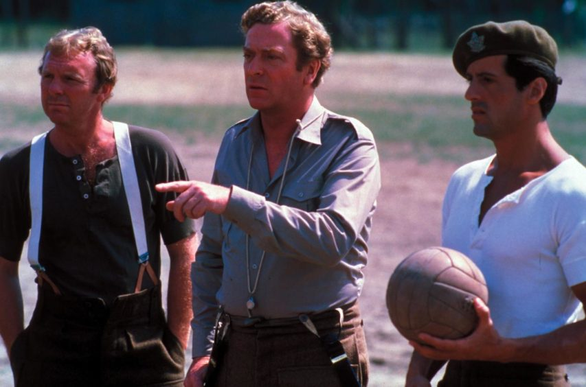 Bobby Moore, Michael Caine and Sylvester Stallone film scenes in the POW camp during shooting of the movie in Budapest in 1980.