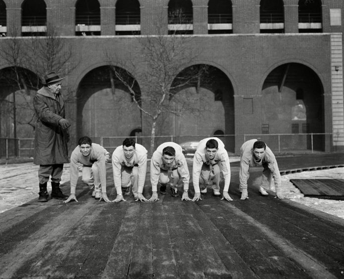 Lawson Robertson, left, the University of Pennsylvania track coach in 1944, puts his first track team hopefuls on their mark.