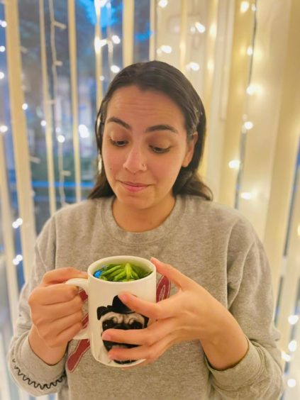 Journalist Ana holding a mug of lettuce tea to answer the question, does lettuce help you sleep?