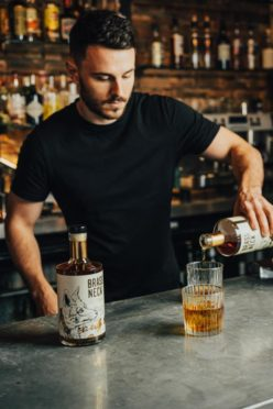 Founder Freddy Drucquer pours a glass of Brass Neck rum.
