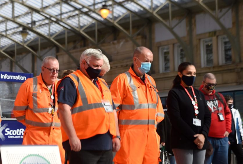 Workmen and staff at Aberdeen station observe the one minute's silence.