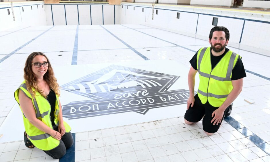 Trustees Fiona Stevenson and Steven Cooper by a Save Bon Accord Baths poster on the bottom of the cleaned pool.