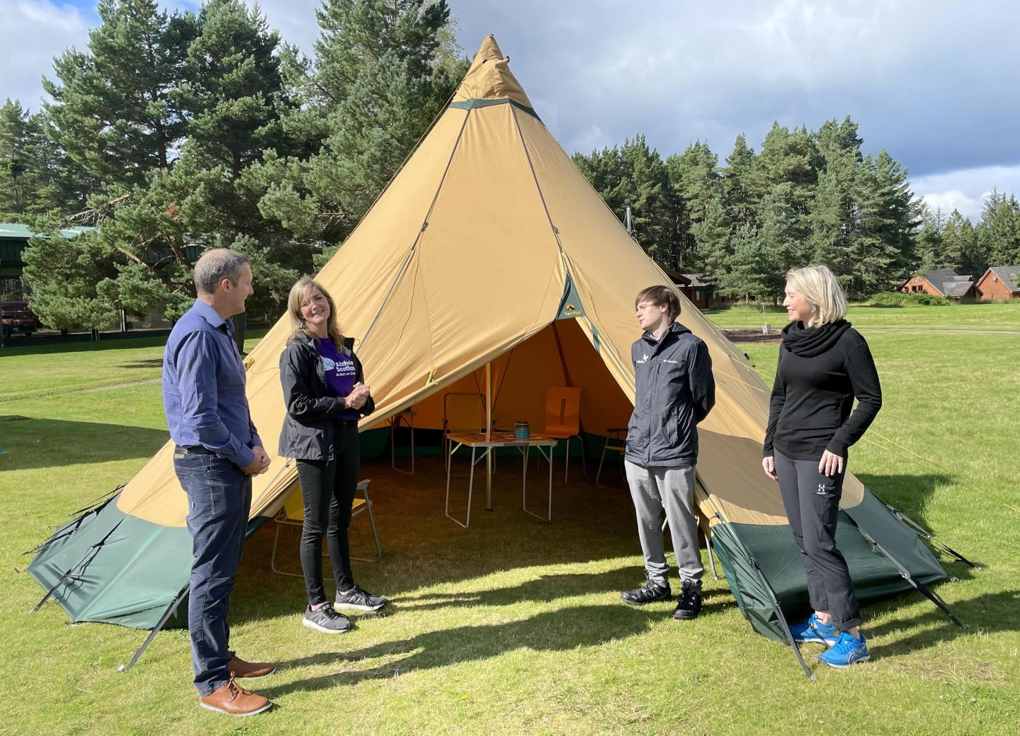 Cabinet Secretary Michael Matheson MSP, Gillian Council (Alzheimer Scotland), Xander McDade (Chair CNPA Board) and Caroline Clark (NLHF Director Scotland) standing at the tipi used for nature sessions with dementia patients.
