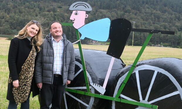 Jenna and Duncan Ross besides Tour of Britain hay bale display in Tarland