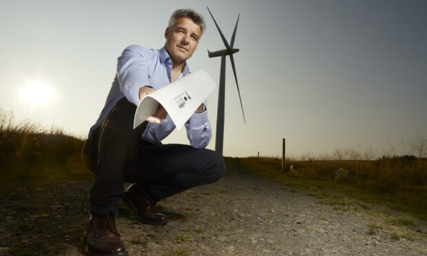 Edge Solutions managing director David Urch holding the armourEDGE in front of a wind turbine.