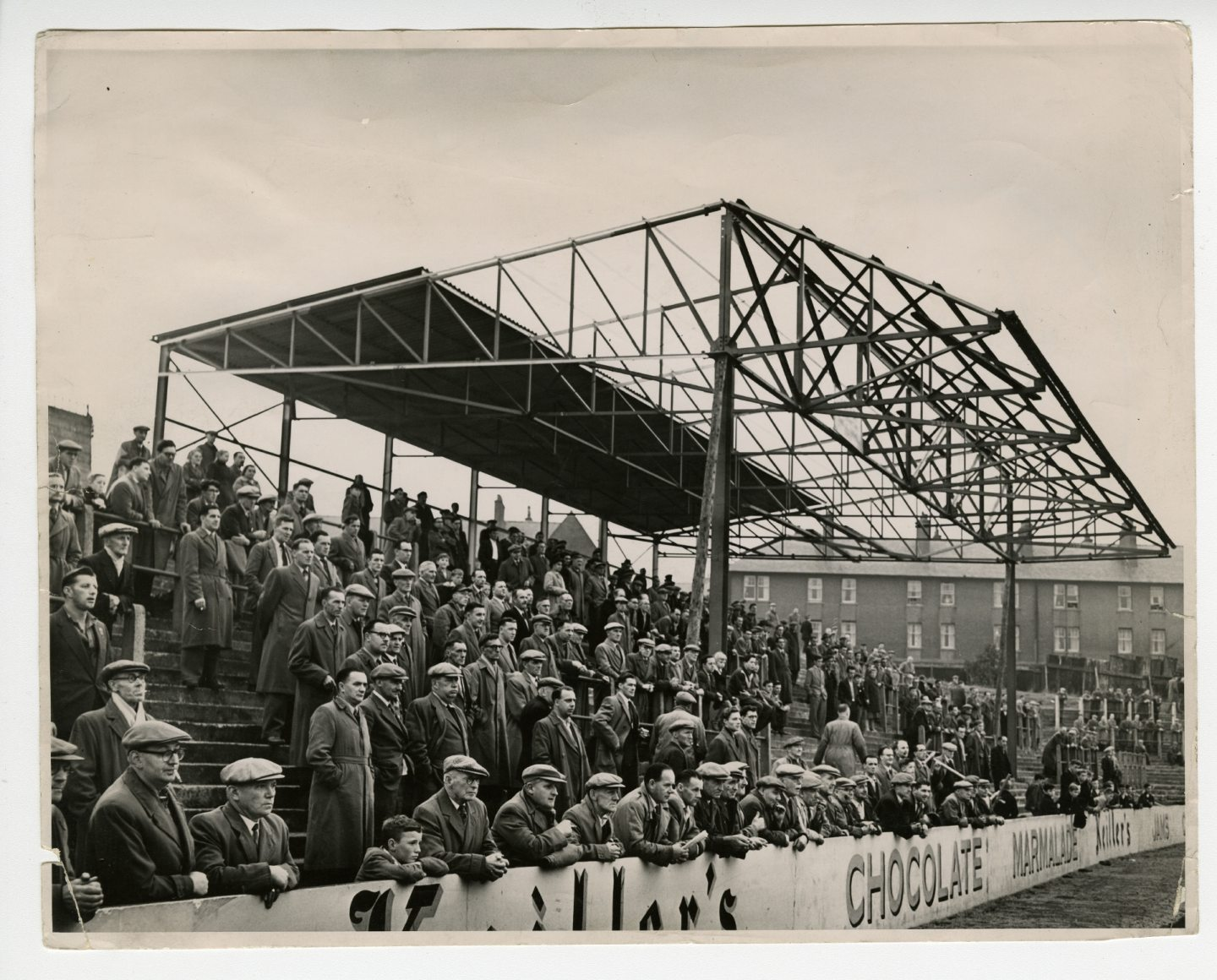 Fans under the new covered enclosure at Tannadice Park in 1957.