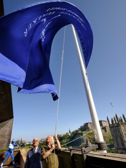 Ivan Menezes, chief executive, Diageo, and Barbara Smith, managing director of Johnnie Walker Princes Street, unfurl a flag to mark the opening.