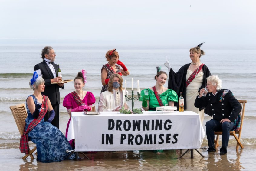 The Extinction Rebellion group, dressed up and sitting at a table on the beach with a tablecloth that reads 'Drowning in Promises'
