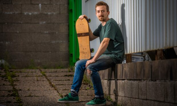 Malcolm Bradley sitting on a brick wall showing off a small skateboard made from cork and wood.