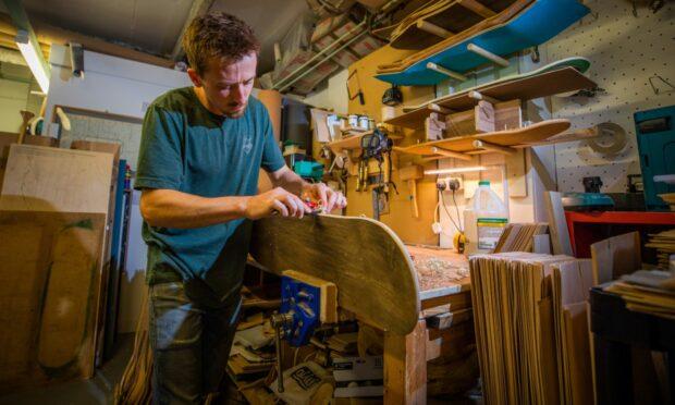 Malcolm Bradley working on a Bonny Company skateboard in his workshop.