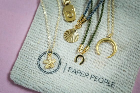 A collection of Paper People jewellery, a flower, a star sign, a shell, a horseshoe and a half moon.