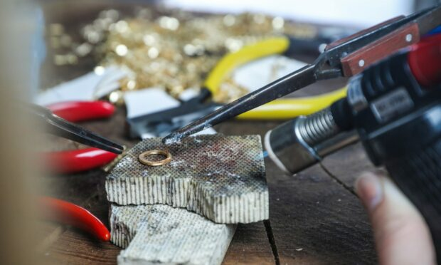 Close-up of soldering a piece of Paper People jewellery.