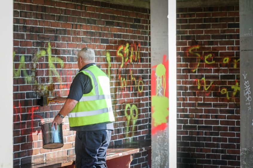 A Dundee City Council worker cleaning the graffiti off the brick walls.