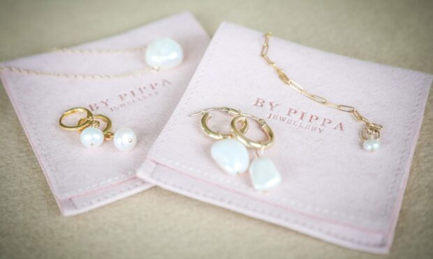 By Pippa earrings and necklaces on pink By Pippa packaging.
