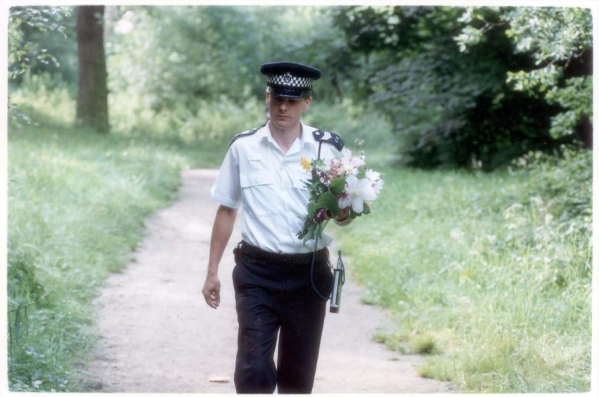 A policeman carrying floral tributes near the scene of Rachel's murder in 1992.